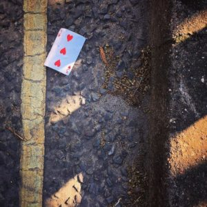 A playing card lies next to a yellow line on a road