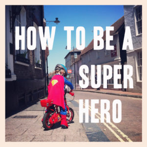 A boy in a superhero csotume rides a bike through the streets of a small town