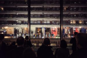 A crowd of people watches a distant performance happening around the Barbican estate, with lighting design by Jon M Armstrong