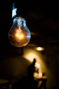 Close-up of a light bulb, with a distant man lit in a mysterious light