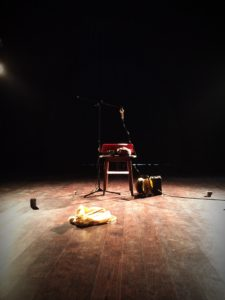 A collection of musical instruments sits on an empty stage