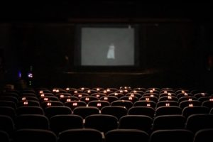 Glowing lights rest on row of theatre seats. In the background a white figure dances behind a screen